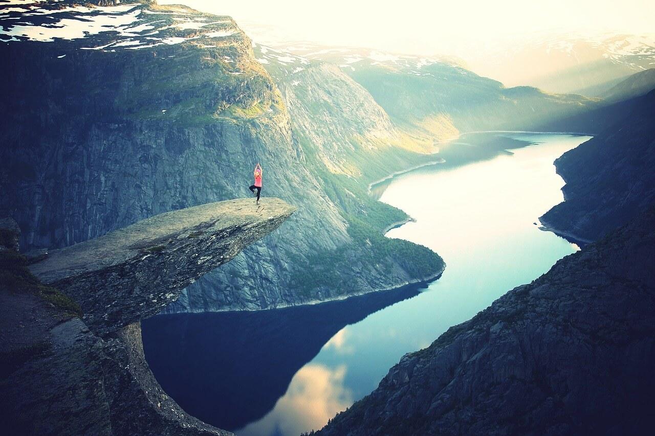 Eine Frau macht Yoga an einer Klippe in Norwegen.