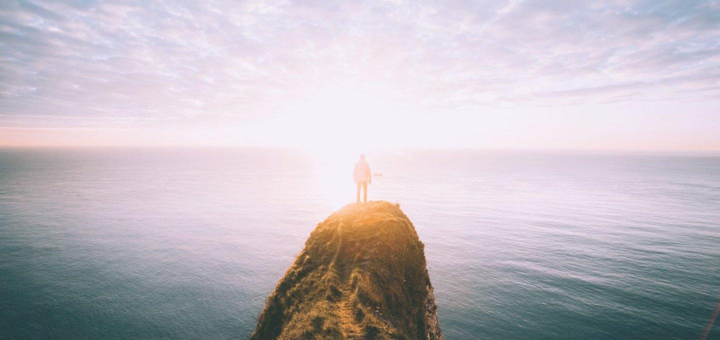 Ein Mann steht an einer Klippe.